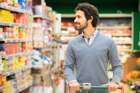 Knappe man winkelen in een supermarkt Stockfoto