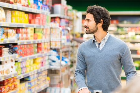 Man choosing the right product in a supermarket Stock Photo