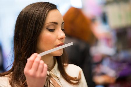 Vrouw die een parfummeetapparaat in een winkel ruikt