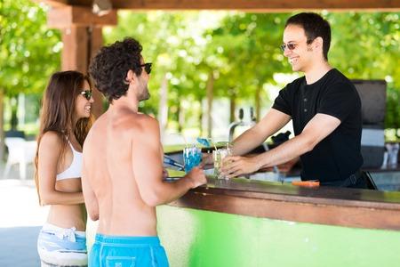 幸せなカップルのビーチのバーでカクテル 2 杯を注文