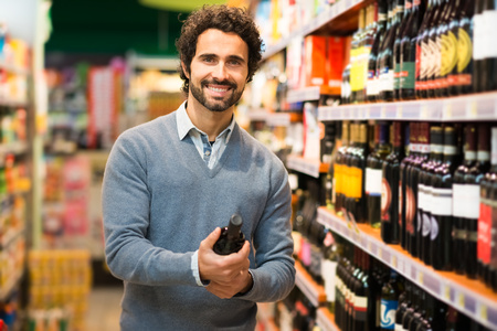 people: Man in a supermarket choosing a wine bottle