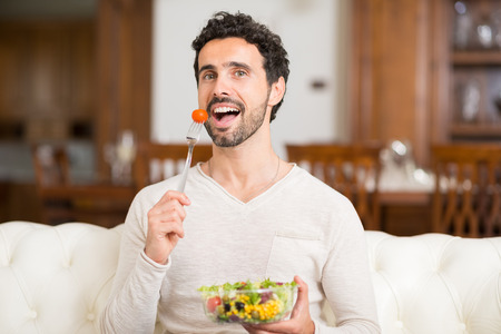 man eating: Portrait of a man eating a salad in his apartment Stock Photo