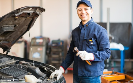 Mechanic holding a wrench while fixing a car in his shop Stock Photo