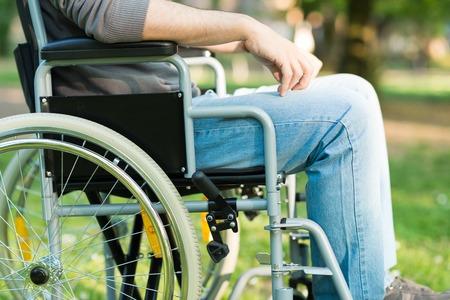 paraplegico: Detalle de un hombre discapacitado con una tableta en un parque Foto de archivo