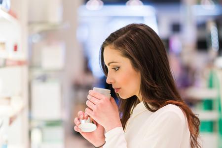 olfato: Retrato de una mujer de compras en una tienda de belleza