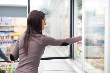 alimentos congelados: Mujer que toma profunda de alimentos congelados de un congelador en un supermercado