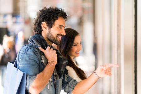 若いカップルは都市通りで買い物に笑みを浮かべてします。男に焦点を当てる、フィールドの浅い深さ