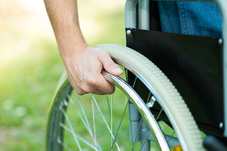 disabled people: Detail of a man using a wheelchair in a park
