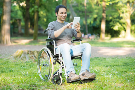 Detail of a man using a wheelchair in a park