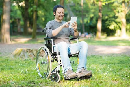 Detail van een man met behulp van een rolstoel in een park Stockfoto
