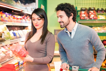 checking ingredients: Young couple shopping in a supermarket