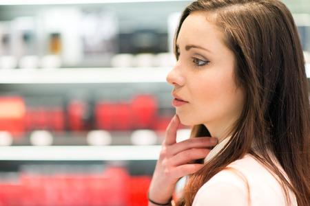 Jonge vrouw winkelen in een schoonheidssalon Stockfoto