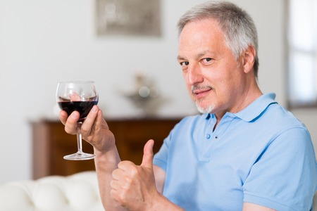 syrah: Mature man drinking a glass of red wine at home and giving thumbs up