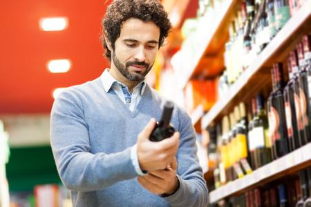 tomando vino: Hombre en un supermercado de elegir una botella de vino