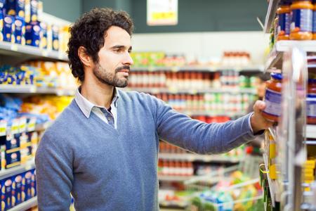 Aantrekkelijke man winkelen in een supermarkt Stockfoto