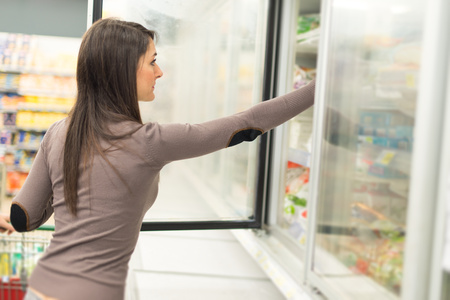 alimentos congelados: Woman taking deep frozen food from a freezer in a supermarket Foto de archivo