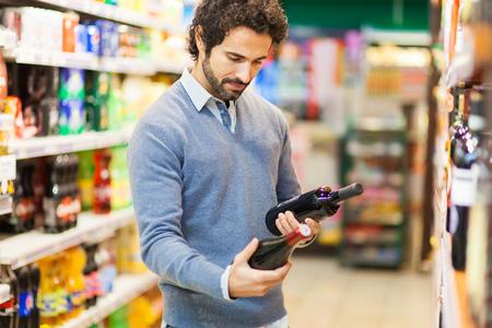 choosing: Man in a supermarket choosing a wine