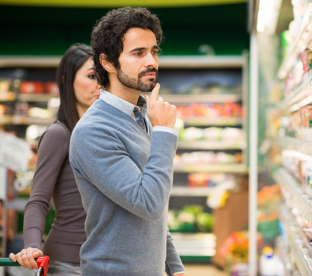 health food store: Handsome man shopping in a supermarket