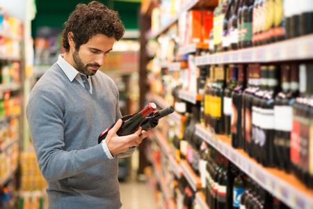 Hombre en un supermercado de elegir un vino Foto de archivo - 55053678