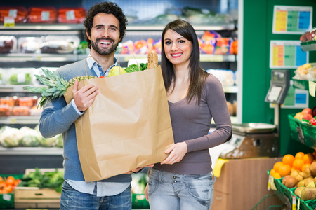 checking ingredients: Couple holding a bag full of food at the supermarket