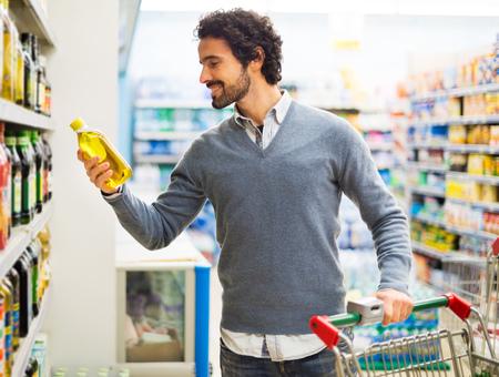 Man die een fles van olie uit een plank in een supermarkt Stockfoto