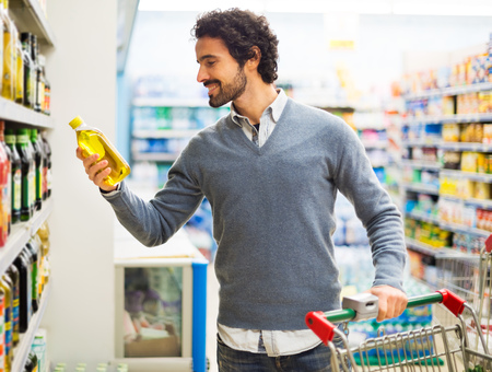 food products: Man taking a bottle of oil from a shelf in a supermarket