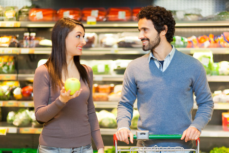 checking ingredients: Couple shopping in a supermarket