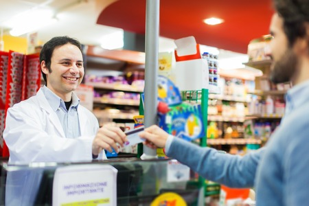 Cliente que usa una tarjeta de crédito para pagar en un supermercado Foto de archivo