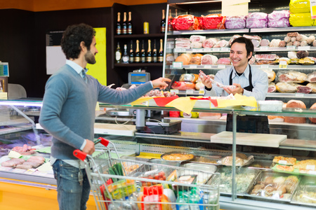 delicatessen: Shopkeeper serving a customer in a grocery store