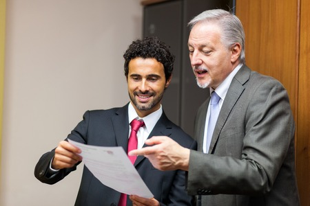 senior business: Businessman showing a document to his colleague