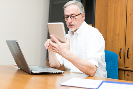 informal clothing: Man using a tablet and a laptop in his office