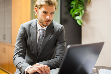 businessman thinking: Businessman using a computer in his office