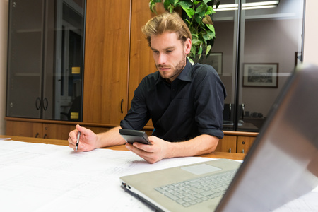 informal clothing: Portrait of a man at work in his office