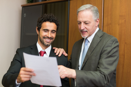 finance director: Businessman showing a document to his colleague