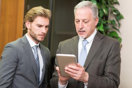 senior men: Business people using a tablet
