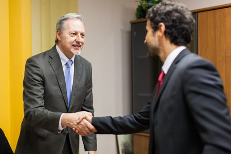 Businessman welcoming a guest in his office Archivio Fotografico