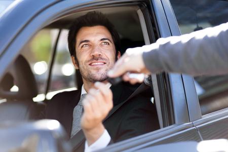 Hombre que toma la llave del coche Foto de archivo - 55147636