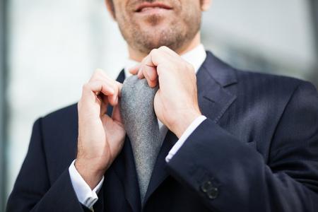 adjusting: Detail of a businessman adjusting his tie