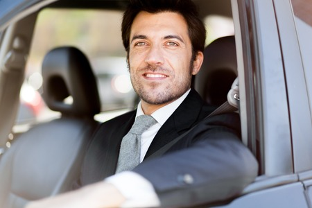 Portrait of an handsome smiling business man driving his car photo