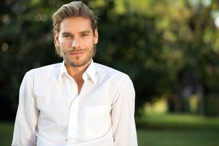 ojos verdes: Retrato de un hombre joven y guapo en el parque Foto de archivo