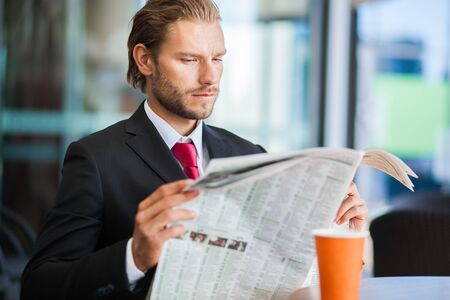 periodical: Handsome man with newspaper and coffee Stock Photo