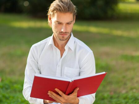 master degree: Young man reading a book outdoor
