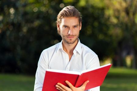 personas leyendo: Hombre joven que lee un libro al aire libre