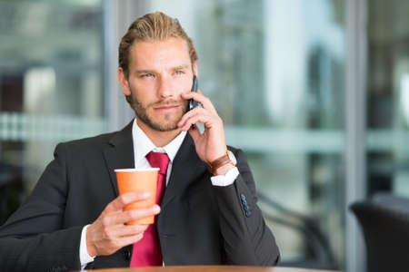 rubia ojos azules: Hombre de negocios haciendo una llamada telefónica mientras el consumo de café