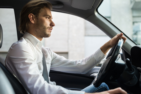 man shirt: Handsome young man driving his car