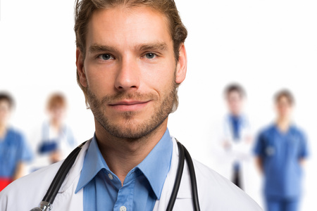 doctoring: Portrait of a smiling handsome doctor in front of his team Stock Photo