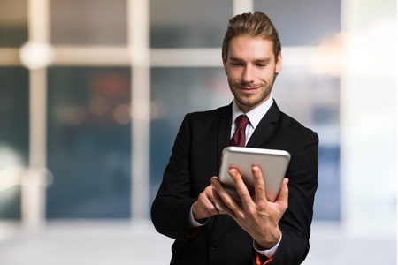 eye pad: Portrait of a smiling businessman using his tablet computer Stock Photo