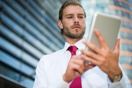 urban environment: Businessman using a digital tablet in an urban environment Stock Photo