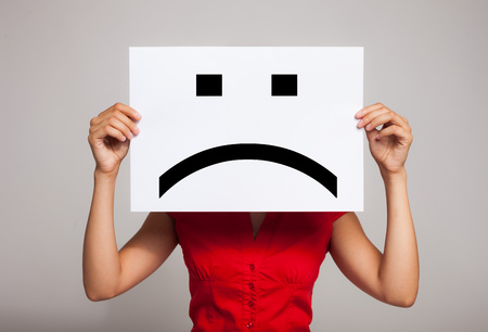 Woman holding a sad face emoticon Standard-Bild