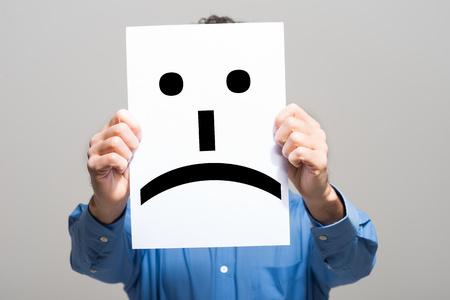 Hombre que sostiene un emoticono cara triste